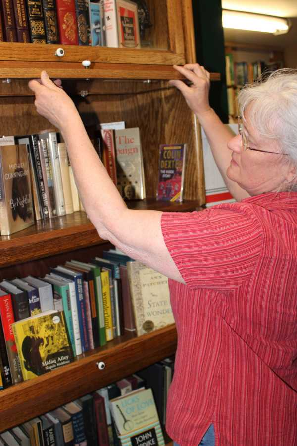Bell's Books owner Faith Bell browses her shop's unique collection of autographed novels. Photo by Madison Mignola.