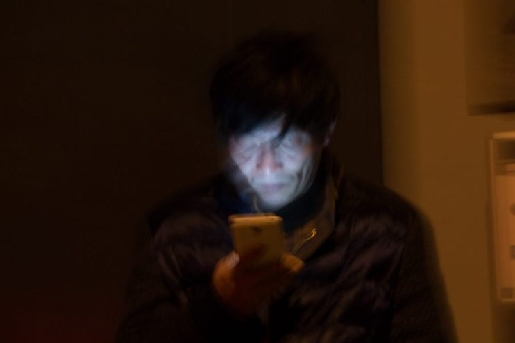 A close-up of a man's face in the dark looking at his phone