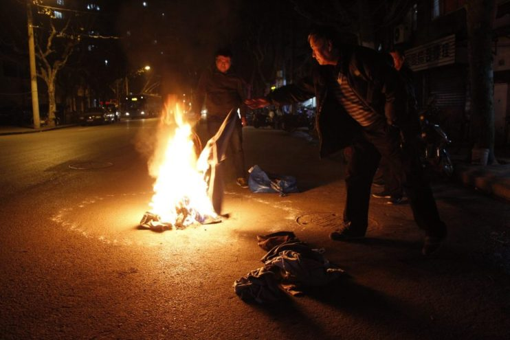 Two men making a fire on a city street