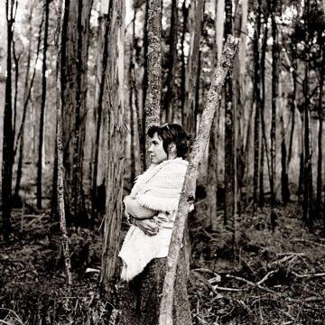 Judith Nangala Crispin leaning on a tree in the Australian bush