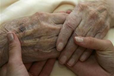 52743-a-young-carer-holds-the-hands-of-an-elderly-woman-in-a-resid