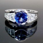 Tapered trapezoid diamonds set around a 1.15 blue sapphire all in platinum.