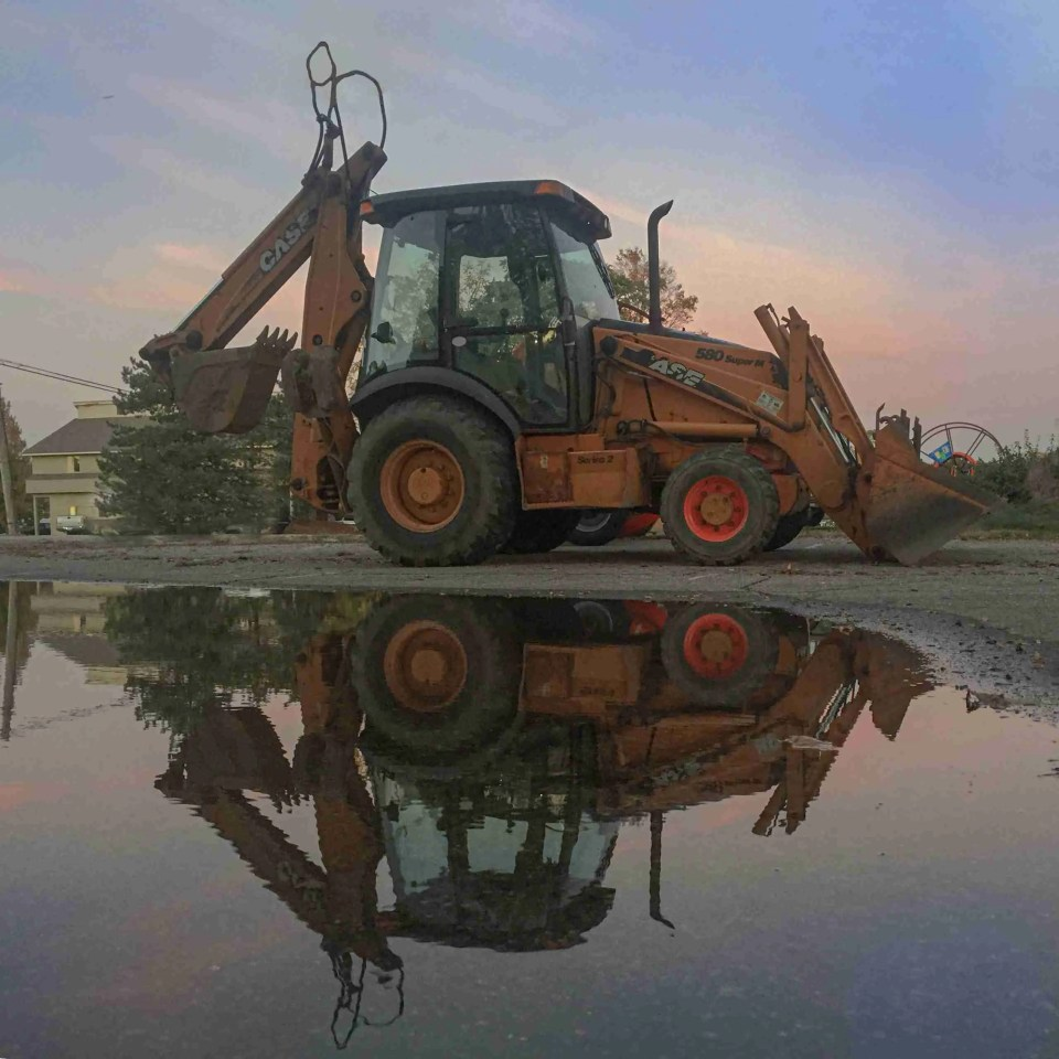 a low angle shot of a bulldozer reflected in a puddle