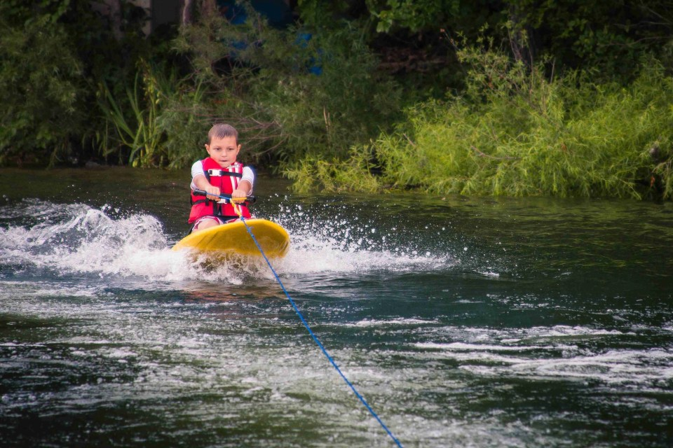A boy riding a knee board behind the boat