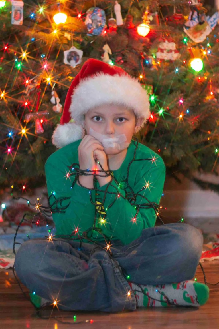 Boy tied up in christmas lights with starburst affect using aperture