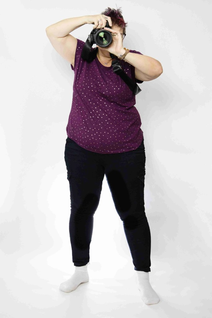 Woman holding camera in an awkward stance
