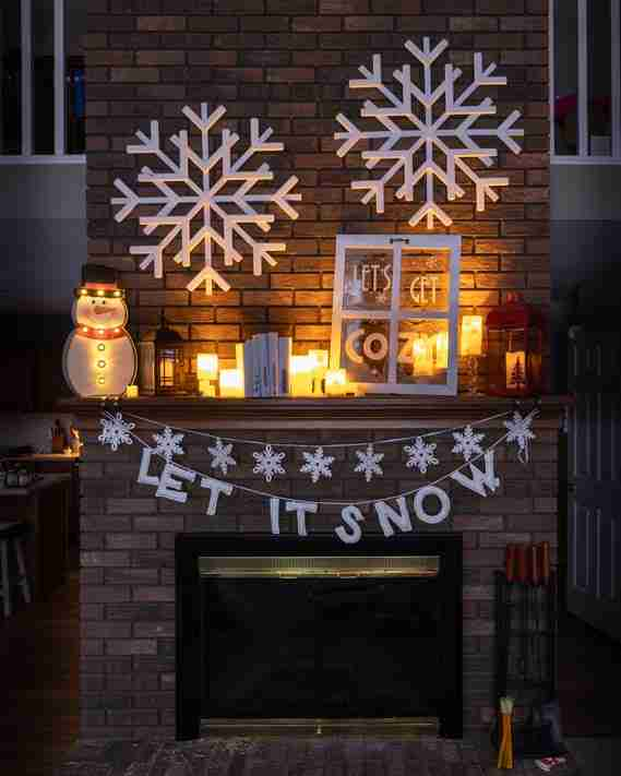 Cozy candlelit fireplace mantle with snowflakes and a frosted window