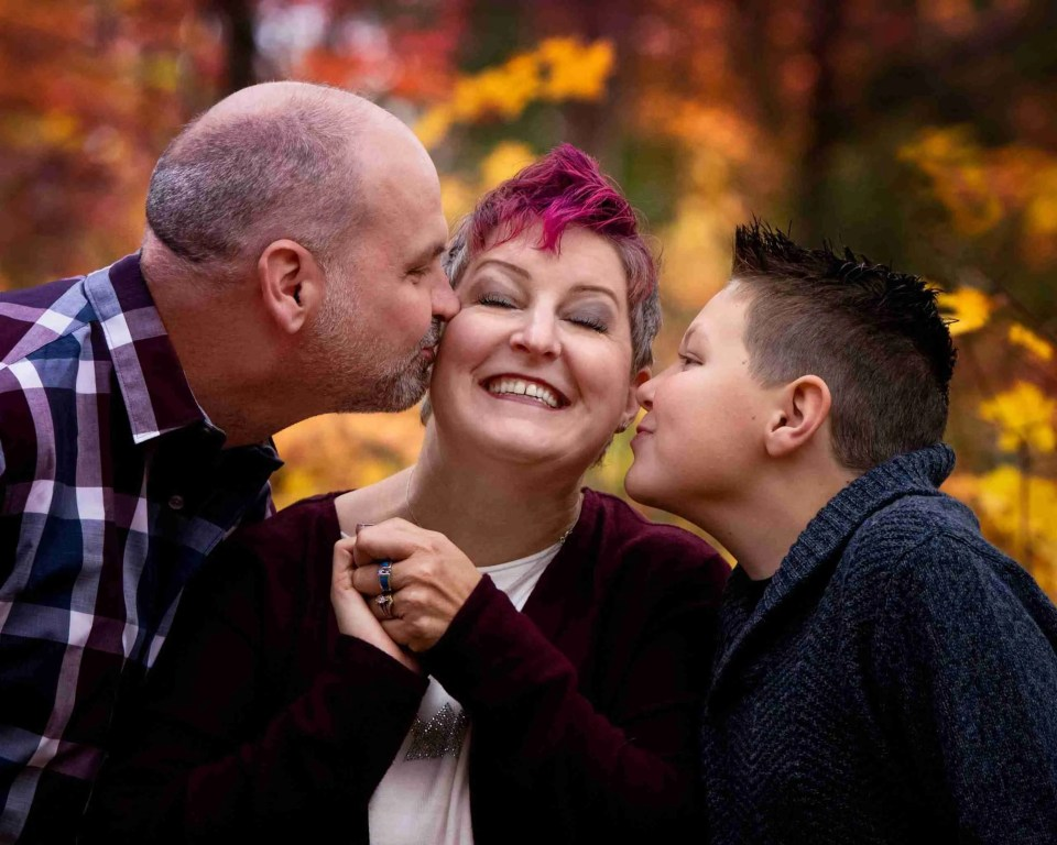 Mom receiving kisses on cheeks from husband and son using give mom the sweetest kisses photography prompt for families