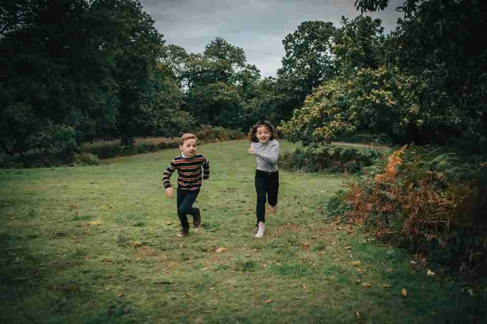 boy and girl racing toward the camera using race to photographer Photography Prompt for Families