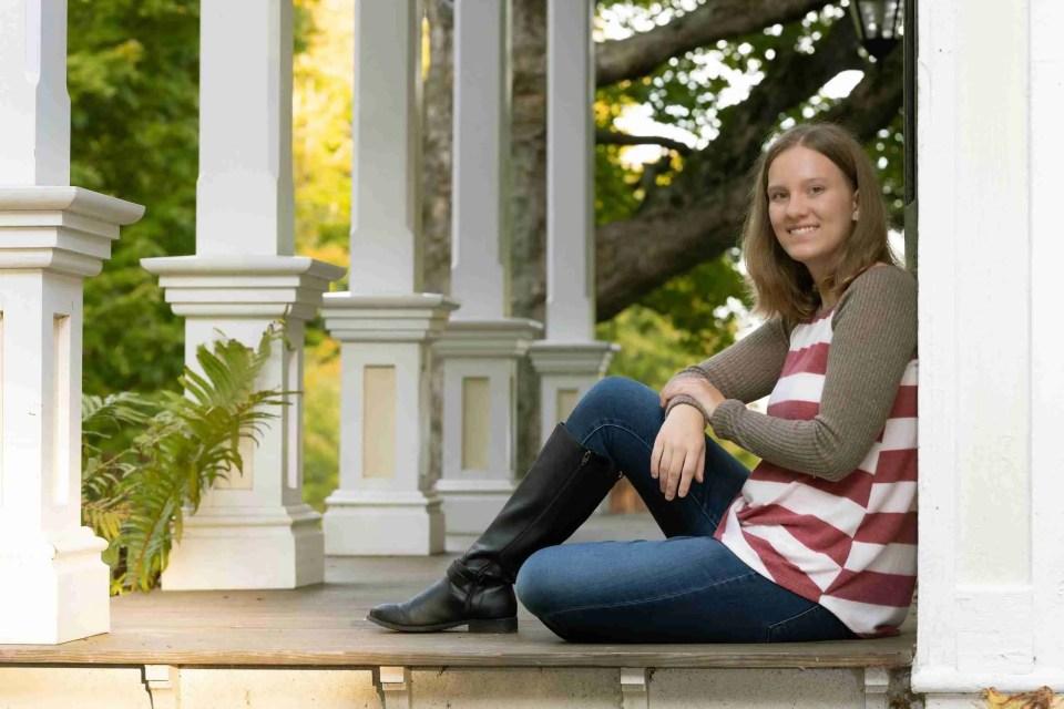 A cute girl pose with a girl sitting against a bridge rail
