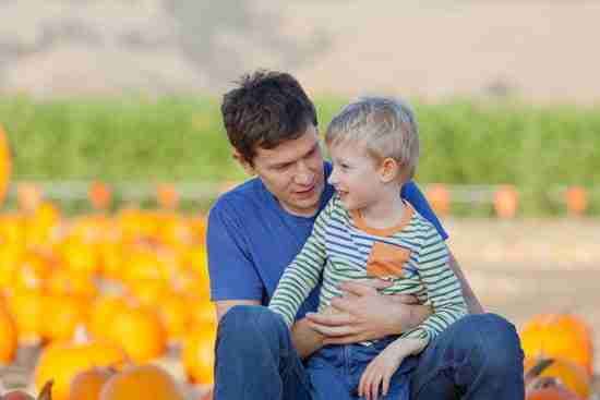 a father and son pose in a pumpkin patch for an autumn photoshoot