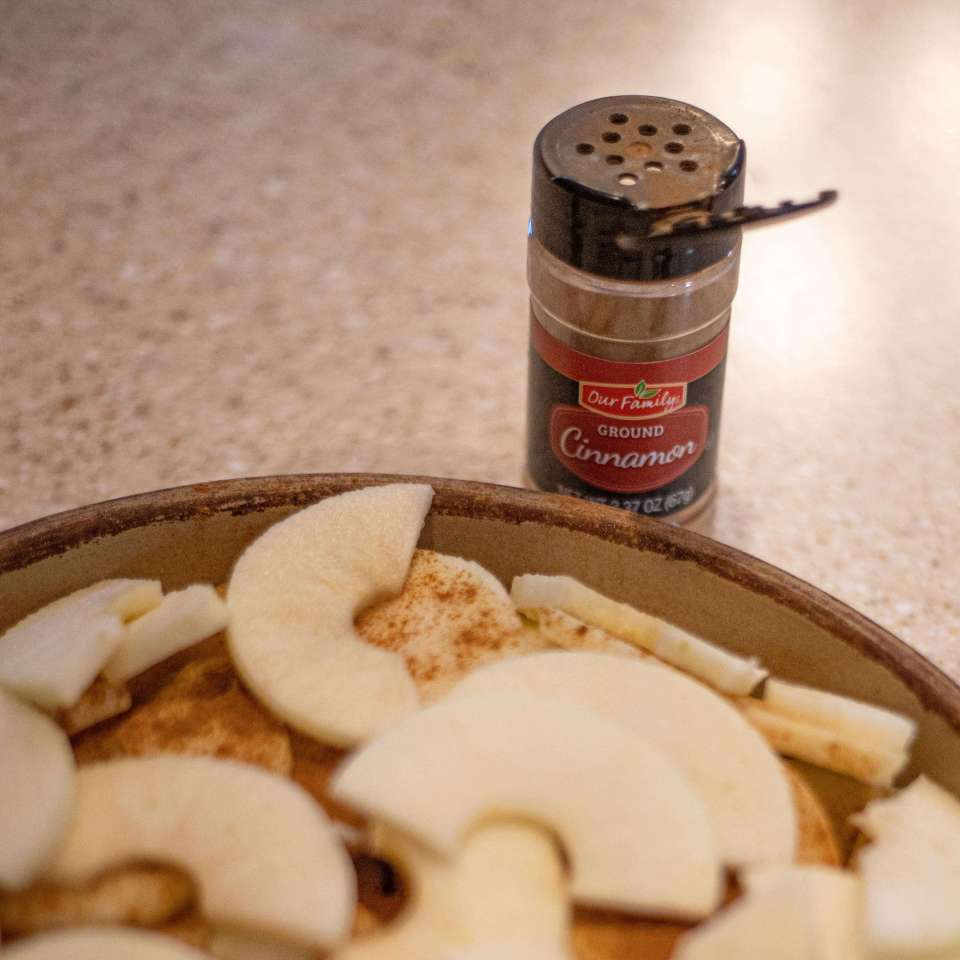 a baking pan with half moon shaped apples sprinkled with cinnamon for grandma's apple crisp