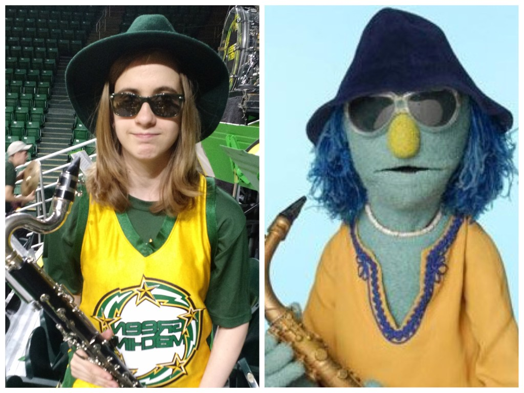 Veronica standing next to a picture of Zoot the muppet. Both are wearing a large hat, yellow shirt, sunglasses, and holding their instruments