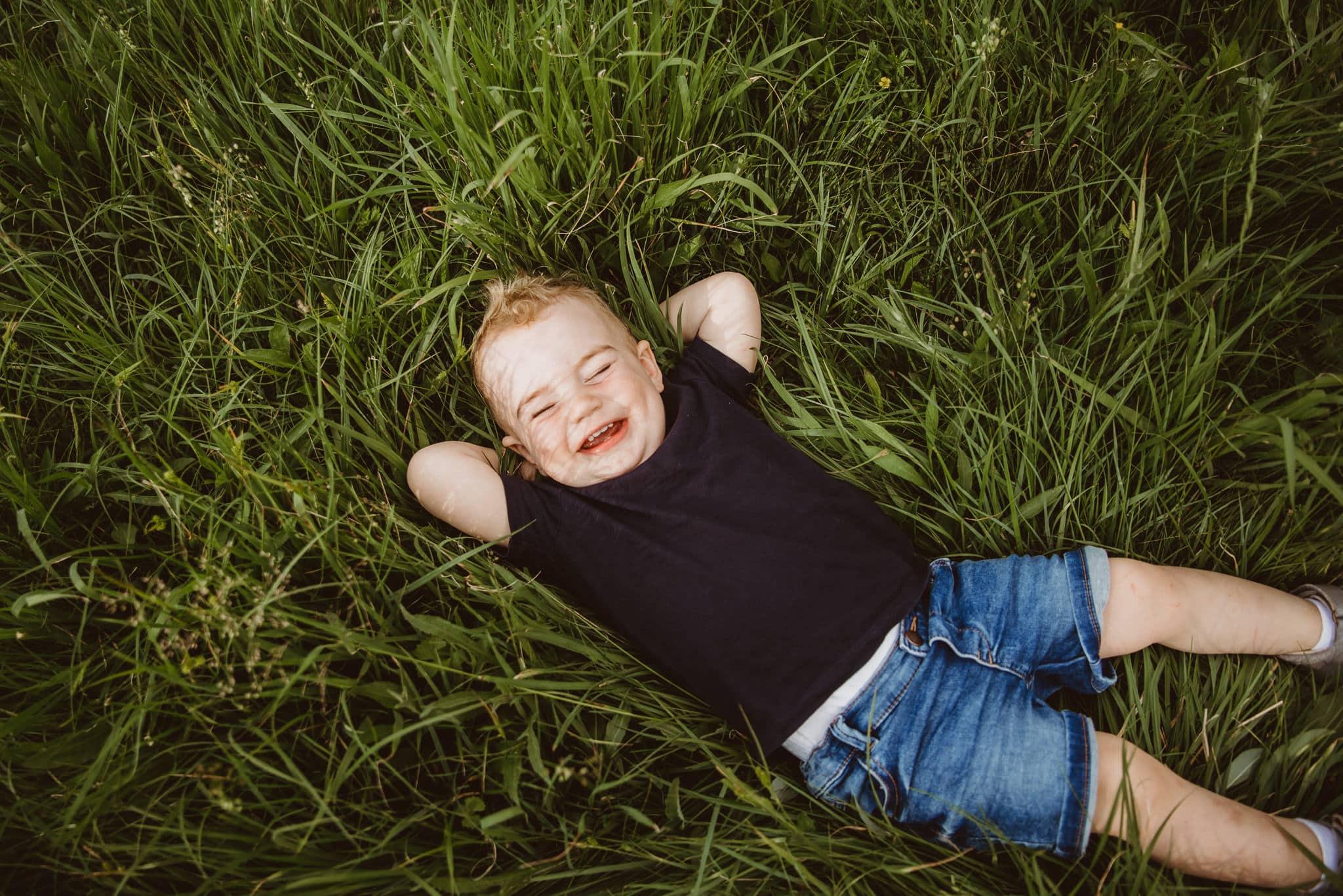 chlapeček ležící v trávě se směje přirozenému rodinnému focení na vysočině