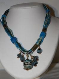 alliance de la soie, du métal gravé et de perles faites au chalumeau.