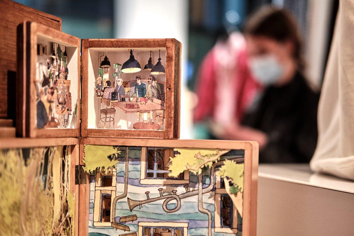 Aufklappbare Kästchen aus Holz, in denen aus Papier Szenen aus der Dresdner Neustadt gestaltet sind