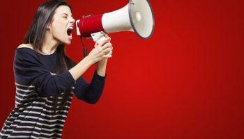 Девушка стоит на красном фоне и кричит в бело-красный мегафон