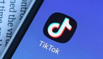 Иконка ТикТок на синем экране смартфона