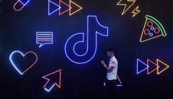 Человек идёт, глядя в телефон, рядом со стеной с логотипом ТикТок