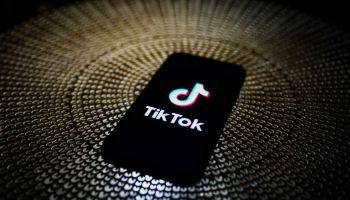 Смартфон с логотипом ТикТока на экране лежит на тёмной блестящей поверхности