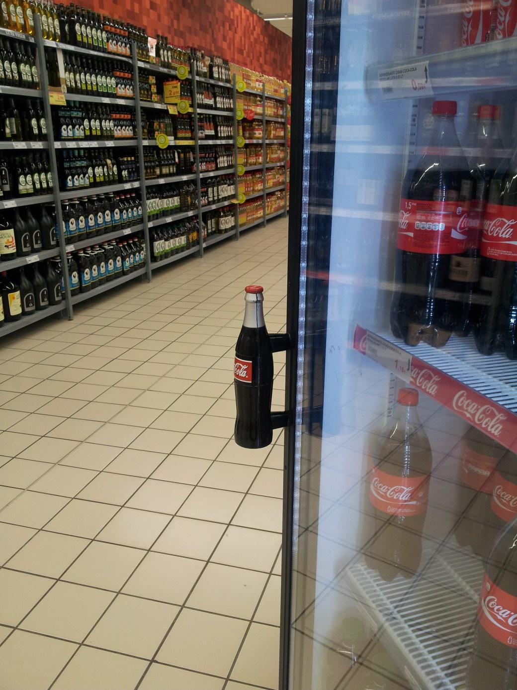 Colaflasche als Türgriff am Kühlschrank