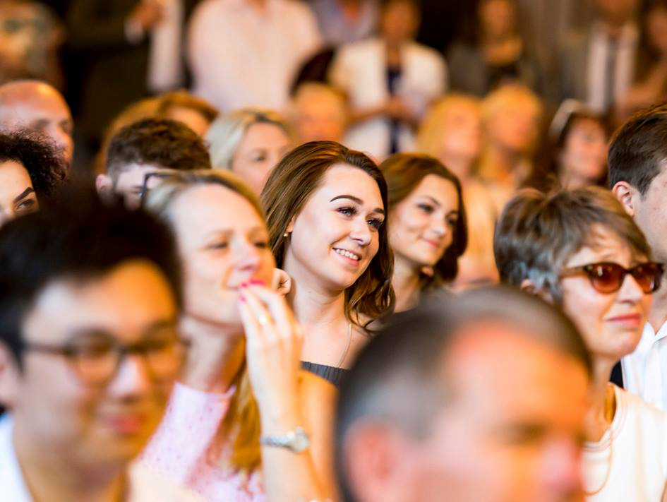 LVS Leavers CelebrationYoung people smile in a crowd as they listen to a speech