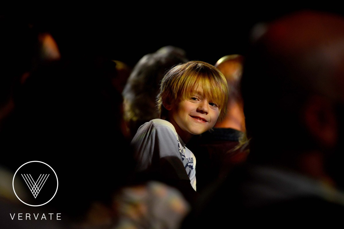 child smiles at camera in a dark circus tent