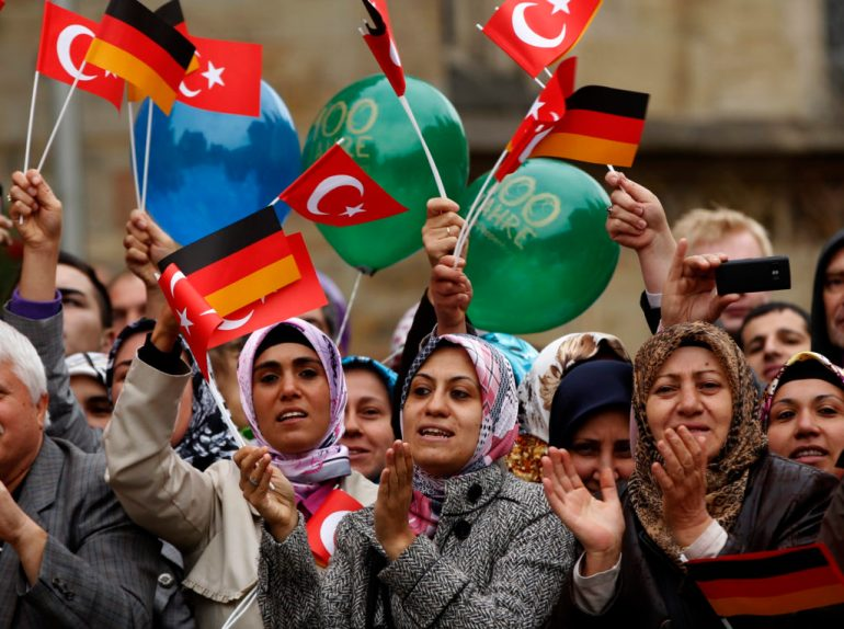 Turkish women wave German and Turkish flags during a visit of Turkey's President Abdullah Gul in Osnabrueck September 20, 2011. REUTERS/Ina Fassbender (GERMANY - Tags: POLITICS) - RTR2RKYD