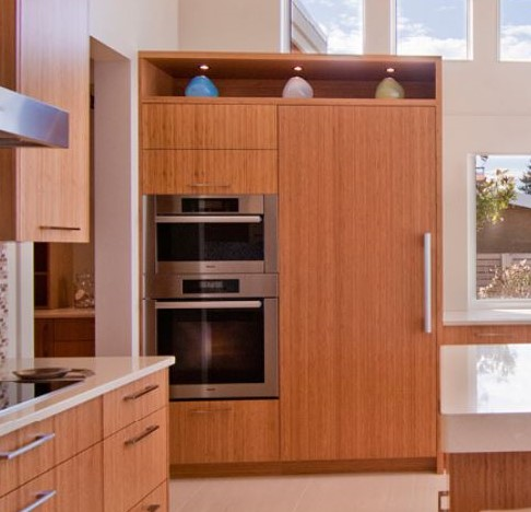 Integrated paneled refrigerator beside double ovens
