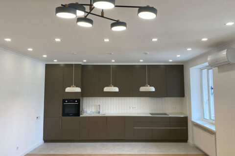 brown kitchen with three lamps and chandelier