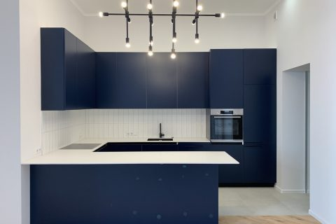 blue kitchen with a chandelier