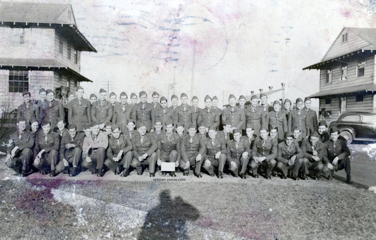 """""""Fort Custer 10__"""" - A 1942 training platoon or company real photo postcard from World War II.  Sent by Pvt. Elmer Stevens (kneeling 5th or 6th from left)."""