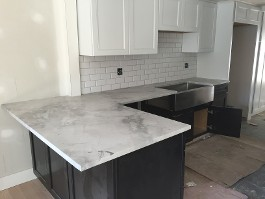 white marble countertop with dark cabinets