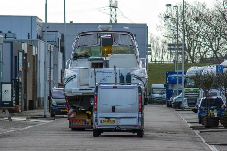 Illustratie: een dieplader met een enorme speedboat rijdt door industrieterrein De Zekken in Hoek van Holland