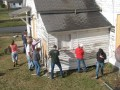 VFC Volunteers from Radford University, scraping and painting a community building.