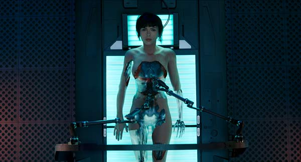 Major Maddy Kisana (Scarlett Johansson) entering the world – her cybernetic parts melded together and then infused through a white milky substance that rips off to reveal her outer suit layer.