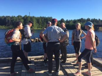 Lentierassa kulttuurikävelyllä. Kuulemme selostusta miten tukin uitto toimi Lieksa-järven vesistöstä Venäjän puolelta Suomeen — paikassa Lendery, Kareliya, Russia.
