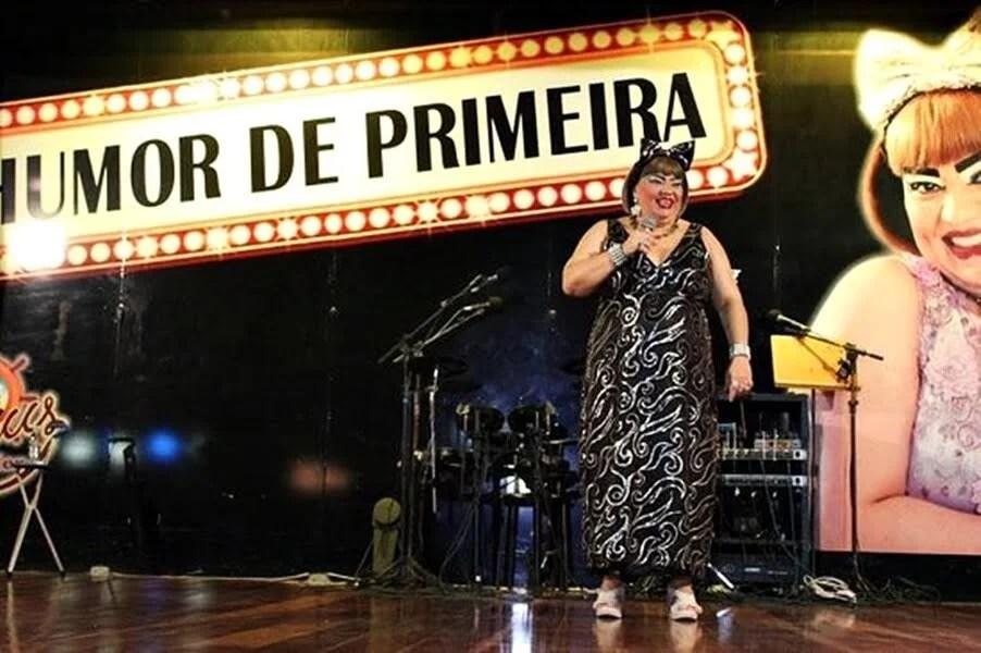 mulher com vestido preto e detalhes em cinza fazendo show de comédia em palco em Fortaleza