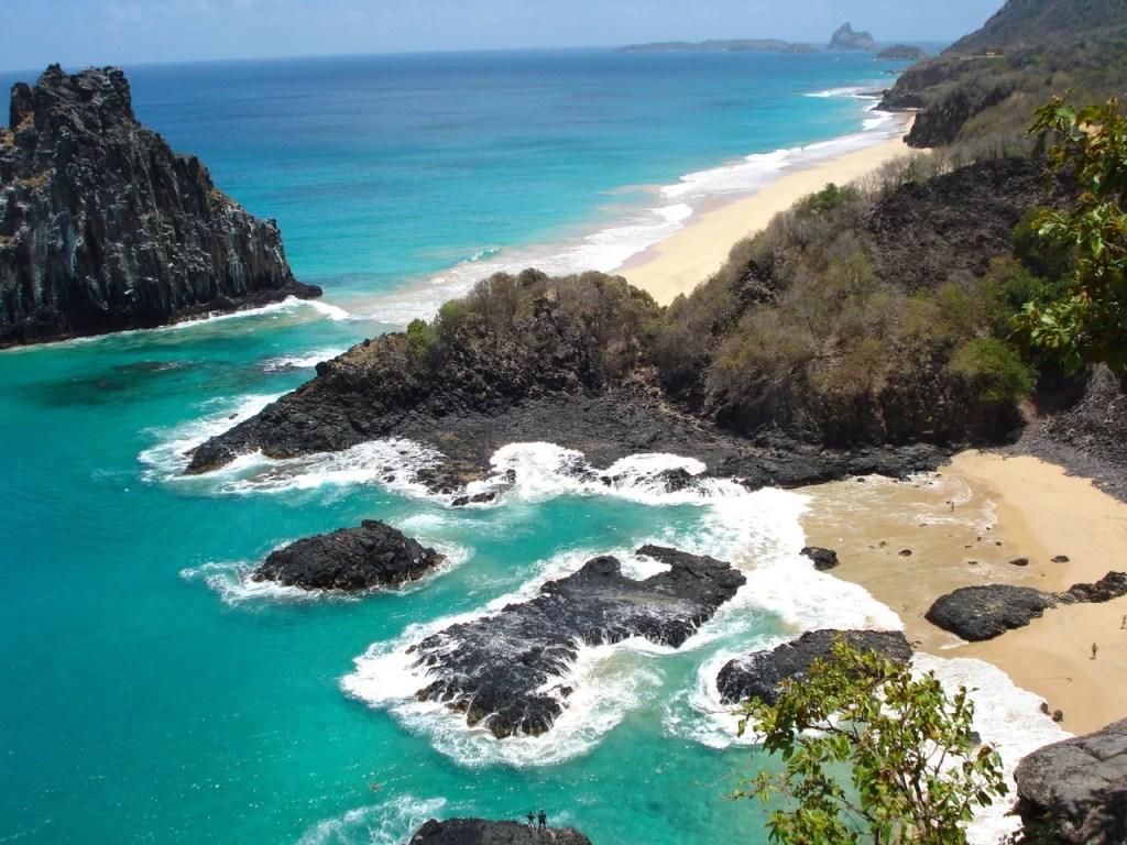 Rochas nas águas da Baia dos Porcos e mar com pequenas ondas em Fernando de Noronha