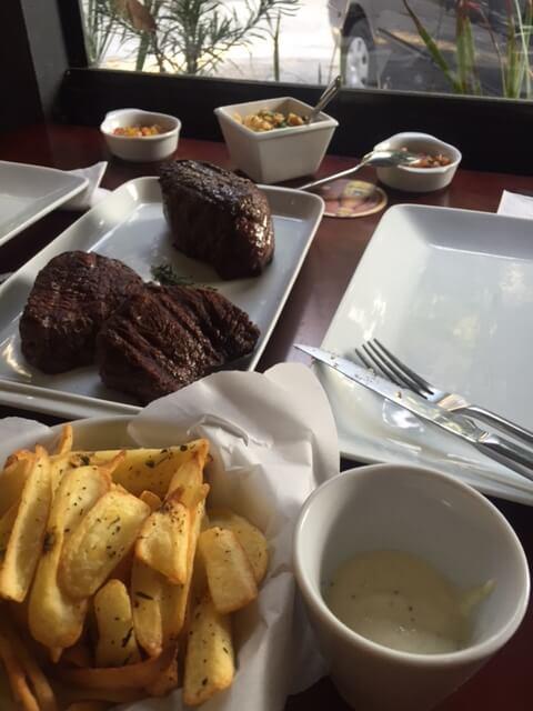 """Os dois pedaços de carne no meio da mesa é o Bombom de Alcatra e a peça sozinha, mais próxima à farofa é o """"Shoulder""""."""