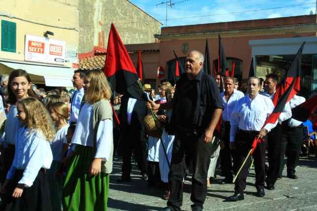 entrano gli anarchici con le loro bandiere rosso/nero