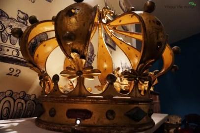 Corona gigante esposta nel percorso dietro le reali stanze di palazzo reale di genova tra gli oggetti dei magazzini del museo.