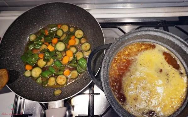 Sui fornelli il riso bolle in acqua e curcuma, mentre le verdure cucinano a parte.
