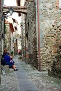 Vicoli di Filetto, uno dei borghi della Lunigiana, con signore sedute.