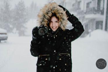 Ragazza con camera che fotografa la neve