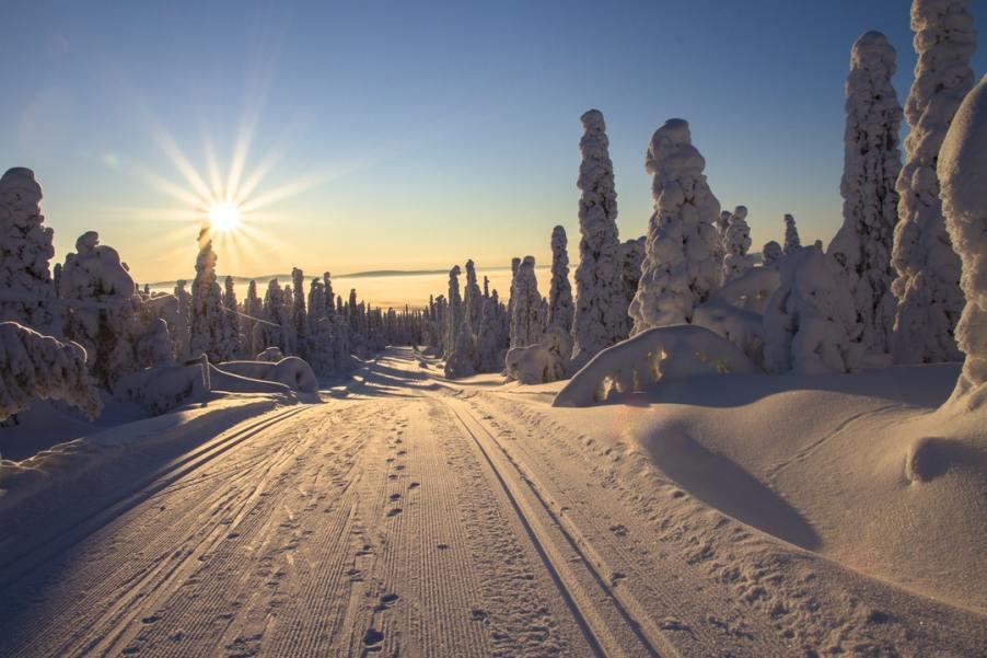Foto di strada con neve e sole basso nel cielo