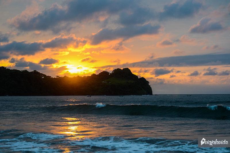 Sol ocultándose detrás de una montaña frente al mar