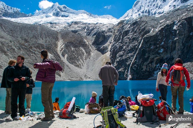 Gente en la montaña frente a la laguna.