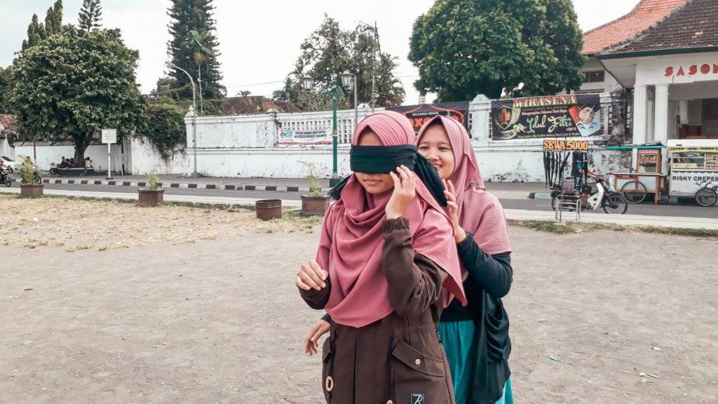 Chica musulmana comprobando la leyenda del parque Alun Alun de Yogyakarta