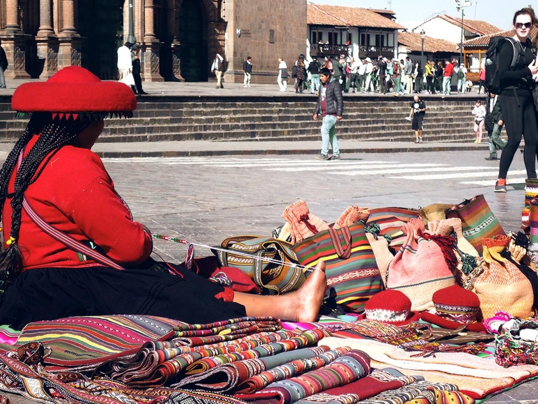 Mujer vendiendo sus artesanías en Cusco
